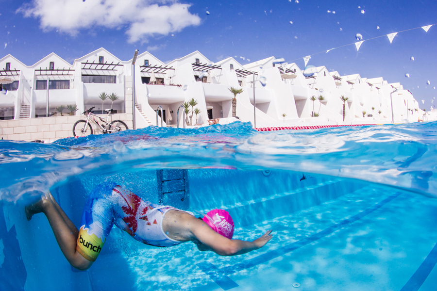 A young boy training hard in the pool to participate in the yearly triatlon while other kids are playing. The image is taken at Sandsbeach resort pool in Lanzarote.